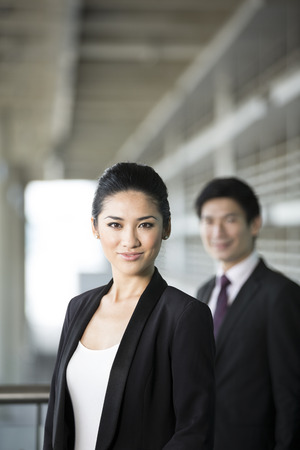 good looking woman: Portrait of a Chinese business woman with a happy expression. Colleague is out focus.