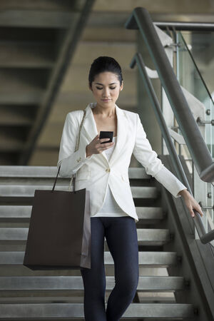 Cheerful Chinese businesswoman reading messages on mobile phone while walking down stairs. photo