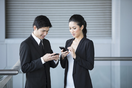 Two Chinese business colleagues talking to each other and using smartphones.