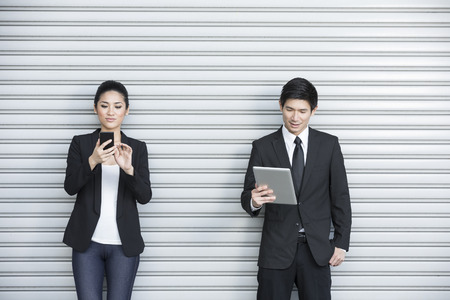 Two Chinese business colleagues using modern portable tech devices  photo