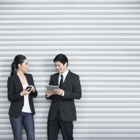 Two Chinese business colleagues using modern portable tech device's Stock Photo - 28190125