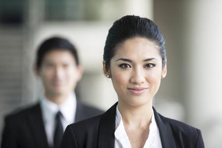 幸せな表情で中国ビジネスの女性の肖像画。同僚は、アウト フォーカスです。
