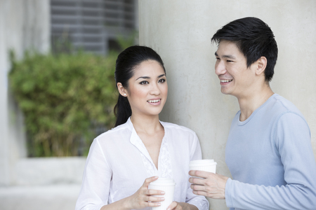 Portrait of an attractive young Chinese couple relaxing together at park. photo