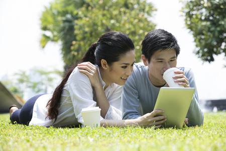 Young Chinese couple using tablet PC in urban city park. Stock Photo