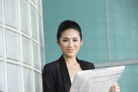 Portrait of a happy Chinese business woman reading a newspaper at office building photo