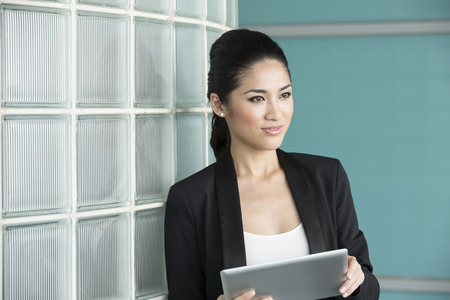 Portrait of a Chinese business woman holding a tablet computer in office. Business woman Looking away thoughtfully. photo