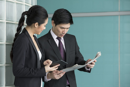 Chinese Business people reading electronic tablet and newspaper. Asian Business man and woman discussing current affairs. photo