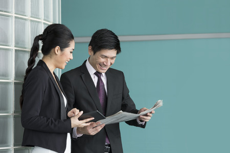 Chinese Business people reading electronic tablet and newspaper. Asian Business man and woman discussing current affairs. Stock Photo