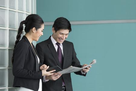 Chinois Gens d'affaires affichant la tablette électronique et le journal. Homme d'affaires et femme asiatiques discuter des affaires courantes.