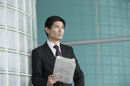 Chinese businessman holding news paper and looking away thoughtfully. photo