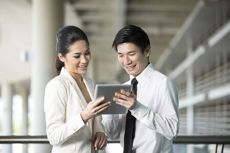 Happy Chinese Business man and woman looking at a digital tablet. Stock Photo
