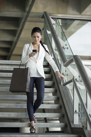 walking down: Cheerful Chinese businesswoman reading messages on mobile phone while walking down stairs. Stock Photo