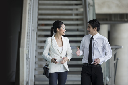 Happy Chinese Business colleagues walking outside office & talking to each other. Stock Photo - 28190376