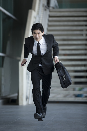 Young Chinese businessman running in urban setting photo