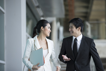asian businessman: Happy Chinese Business colleagues walking outside office & talking to each other.