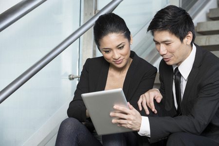 Happy Chinese Business man and woman looking at a digital tablet. photo