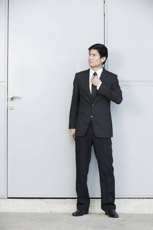 Portrait of a Chinese businessman standing next to a door. photo