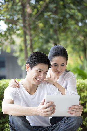 Young Chinese couple using tablet PC in urban city park. photo