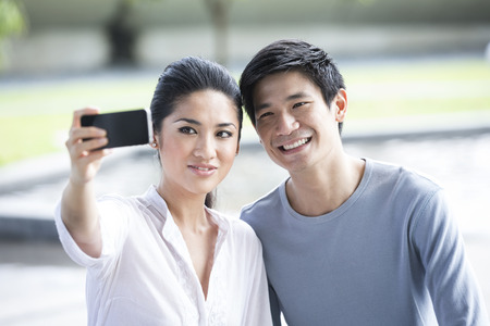 Young Chinese couple using tablet to take a selfie at the park.