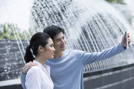 Young Chinese couple using tablet to take a selfie at the park.  photo