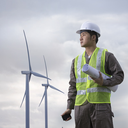 environmental safety: Portrait of a male Chinese industrial engineer at work checking winturbines