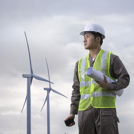 molinos de viento: Retrato de un ingeniero industrial chino masculino en el trabajo de comprobar winturbines
