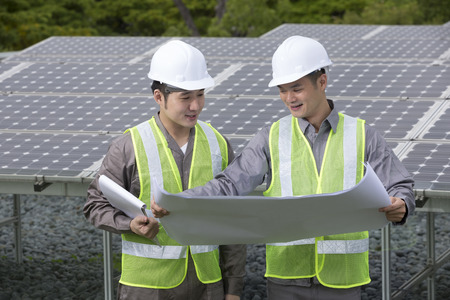 solarpanel: Portrait of two male Chinese solar-panel engineers looking at techincal drawing plans.