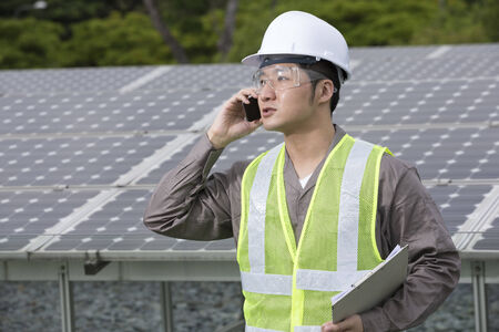 enquiry: Chinese engineer checking solar panel setup and making a phone enquiry. Male Engineer checking photovoltaic installation.
