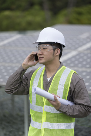 Chinese engineer checking solar panel setup and making a phone enquiry. Male Engineer checking photovoltaic installation.