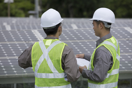 solar power plant: looking over the shoulder of two Chinese maintenance engineers discussing solar panels. Stock Photo