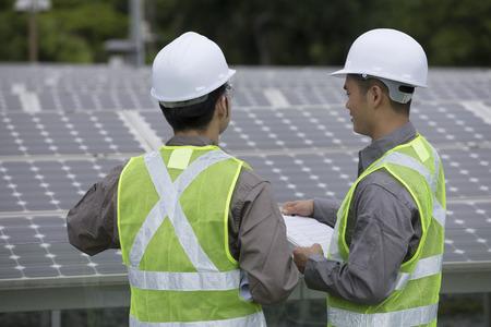 regardant par-dessus l'épaule de deux ingénieurs de maintenance chinois discuter des panneaux solaires.