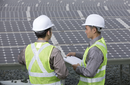 looking over the shoulder of two Chinese maintenance engineers discussing solar panels. Stock Photo