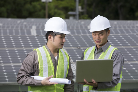 Chinese engineers checking solar panel setup. Male Engineer checking photovoltaic installation with laptop. Stock Photo