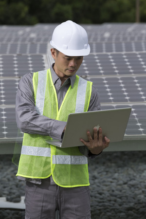 Chinese engineers checking solar panel setup. Male Engineer checking photovoltaic installation with laptop.   photo