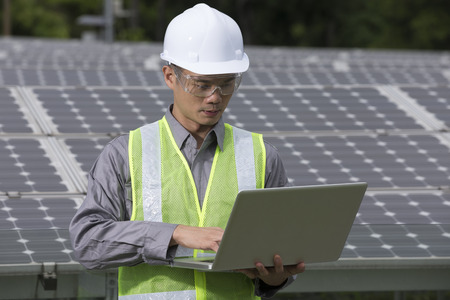 computer engineer: Chinese engineers checking solar panel setup. Male Engineer checking photovoltaic installation with laptop.