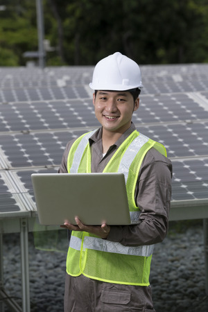 solarpanel: Chinese engineers checking solar panel setup. Male Engineer checking photovoltaic installation with laptop.