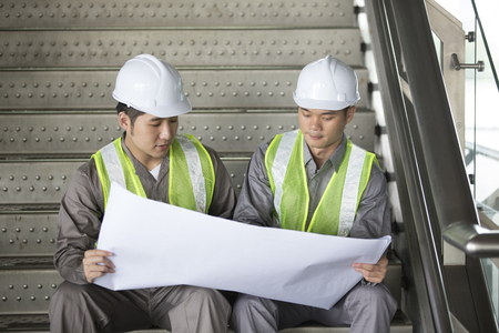 construction plant: Portrait of two male Chinese industrial engineers looking at techincal drawing plans.