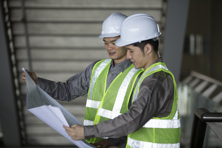 techincal: Portrait of two male Chinese industrial engineers looking at techincal drawing plans.