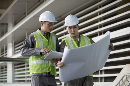 Portrait of two male Chinese industrial engineers looking at techincal drawing plans. photo