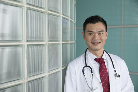 Portrait of a happy Chinese doctor wearing white lab coat with Stethoscope. Medical people portrait. photo