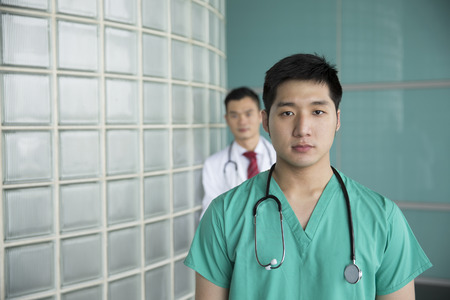Portrait of two happy Chinese doctors wearing hospitail unifroms Stethoscope. Medical people portrait. photo