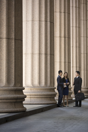 Asian or Chinese business colleagues. Professional Lawyer or business team outside a Colonial building.  Stock Photo