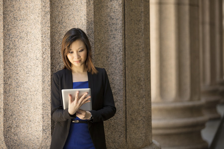 Asian or Chinese woman. Professional Lawyer or businesswoman outside a Colonial building using a digital tablet PC.
