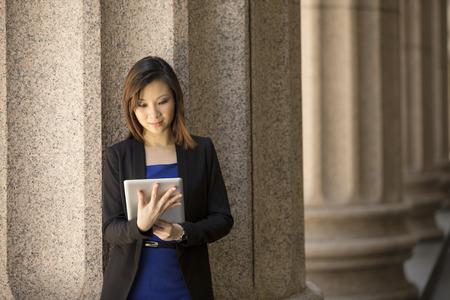 colonial building: Mujer asi�tica o china. El abogado profesional o de negocios fuera de un edificio colonial usando un Tablet PC digital. Foto de archivo