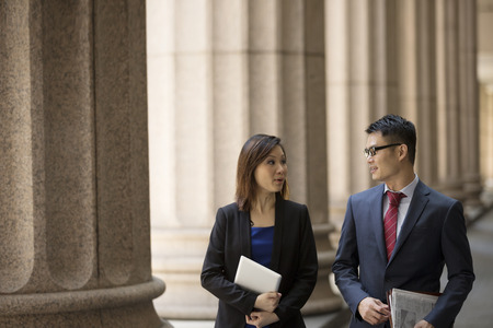 solicitor: Asian or Chinese business colleagues. Professional Lawyer or business team outside a Colonial building.  Stock Photo