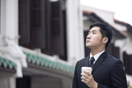 Chinese business man in Asian city. Asian businessman smiling & looking away with blurred Chinese heritage building in background.