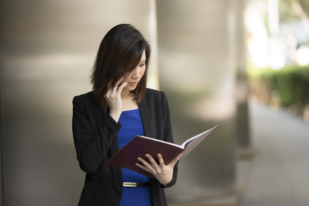 Portrait of an Chinese businesswoman standing outside using mobile phone and reading from notebook photo