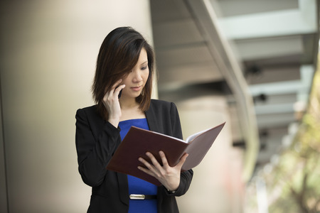 Portrait of an Chinese businesswoman standing outside using mobile phone and checking notebook photo