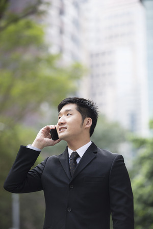 Chinese business Man using his cell phone outdoors in modern Asian city. photo