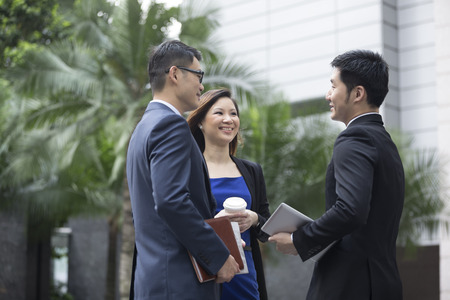 asian businessman: Happy Chinese Business colleagues outside the office talking to each other. Stock Photo
